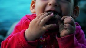 Bebé que juega y que come los guijarros que se sientan en la orilla del río almacen de metraje de vídeo