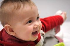 Bebé que juega y que sonríe Imagen de archivo