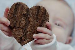 Bebé que lleva a cabo el corazón Imagenes de archivo