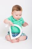 Bebé que lleva a cabo la letra D que mira abajo Fotos de archivo libres de regalías