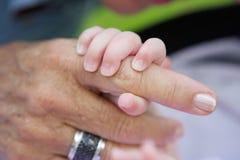Bebé que lleva a cabo la mano de la abuela Imagen de archivo libre de regalías