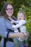 Bebé que lleva de la mamá con el portador, disfrutando del día en el parque Fotografía de archivo libre de regalías