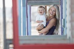 Bebé que lleva de la mujer hermosa en el pórtico Imagenes de archivo
