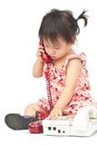 Bebé que marca el teléfono amarillento viejo que llama a la mama Foto de archivo libre de regalías