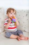 Bebé que mastica en el juguete Imagenes de archivo