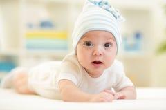 Bebé que miente en cama en cuarto de niños Foto de archivo libre de regalías