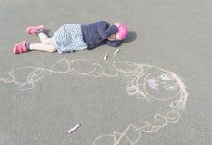 Bebé que miente en el pavimento que piensa en mamá Foto de archivo