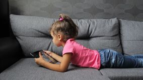 Bebé que miente en el sofá con la tableta El jugar de mentira de la niña en la tableta almacen de metraje de vídeo