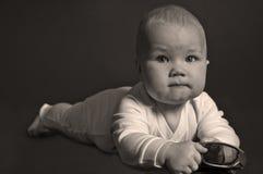 Bebé que miente en el suelo y las miradas en usted Foto de archivo