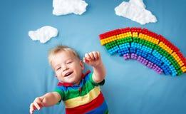 Bebé que miente en la manta con el arco iris y las nubes Imagen de archivo