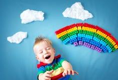 Bebé que miente en la manta con el arco iris y las nubes Fotografía de archivo libre de regalías