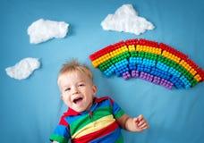 Bebé que miente en la manta con el arco iris y las nubes Imágenes de archivo libres de regalías