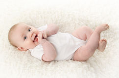 Bebé que miente en la sonrisa posterior Foto de archivo