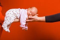 Bebé que miente en los brazos de la madre y del padre Imagenes de archivo