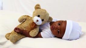 Bebé que miente en pesebre con el oso de peluche almacen de video