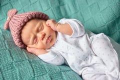 Bebé que miente en su detrás recubrimiento de sus oídos foto de archivo libre de regalías