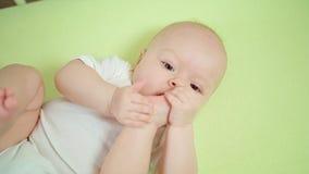 Bebé que miente en un pesebre en casa que come sus dedos del pie metrajes