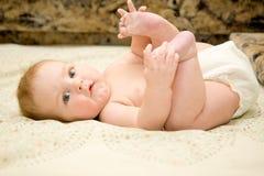 Bebé que miente encendido detrás imagen de archivo libre de regalías