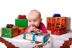 Bebé que miente entre los regalos de la Navidad Imagen de archivo