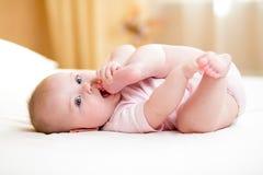 Bebé que miente y que tira de las piernas a su boca Fotografía de archivo libre de regalías