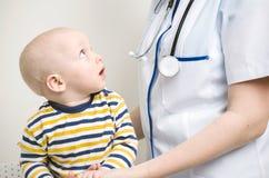 Bebé que mira al doctor Fotos de archivo