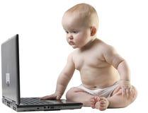 Bebé que mira algo en la computadora portátil. fotos de archivo libres de regalías