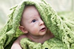 Bebé que mira a escondidas de debajo la manta Imagen de archivo libre de regalías