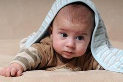 Bebé que mira hacia fuera de debajo la manta Foto de archivo