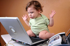 Bebé que mira la computadora portátil desconcertada Foto de archivo