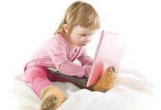 Bebé que mira sobre la pantalla de la computadora portátil Imagen de archivo libre de regalías