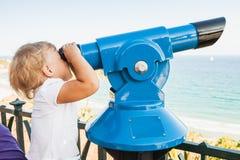 Bebé que mira a través de un telescopio pagado Imagen de archivo