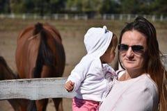 Bebé que mira una manada del caballo en tiempo de la consumición foto de archivo