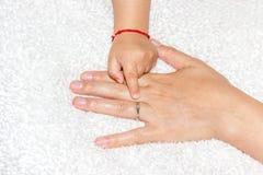 Bebé que muestra el anillo de compromiso de la madre Imagen de archivo