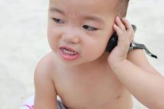 Bebé que murmura en el teléfono celular, grinnig, mirando a la izquierda. Fotografía de archivo