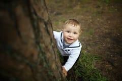 Bebé que oculta detrás de árbol en parque Fotos de archivo libres de regalías