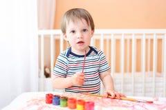 Bebé que pinta en casa Imagen de archivo