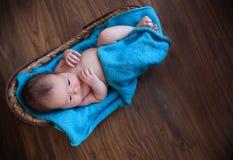 Bebé que pone en la manta azul en la cesta Foto de archivo libre de regalías