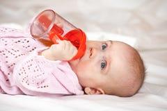 Bebé que pone la botella de bebé del witn Foto de archivo libre de regalías