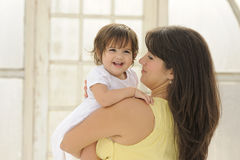 Bebé que ríe en los brazos de la madre Fotografía de archivo libre de regalías