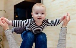 Bebé que ríe nerviosamente para arriba en rodillas del adulto Imagen de archivo libre de regalías