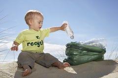 Bebé que recoge la botella en la bolsa de plástico en la playa Foto de archivo libre de regalías