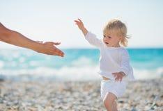 Bebé que recorre a las manos outstretched madres Fotografía de archivo libre de regalías