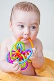 Bebé que roe el juguete multicolor en la toalla amarilla Imagen de archivo libre de regalías