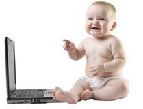 Bebé que señala y que trabaja de risa en la computadora portátil. imagenes de archivo