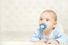 Bebé que se acuesta en el estómago y que aumenta a la cabeza sobre blanco, muchacho del niño Imagen de archivo libre de regalías