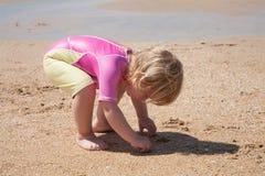 Bebé que se agacha en la playa de la arena Fotos de archivo libres de regalías