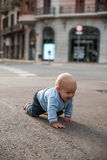 Bebé que se arrastra en la calle y la sonrisa Imagen de archivo