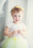 Bebé que se coloca cerca de la ventana Fotos de archivo libres de regalías