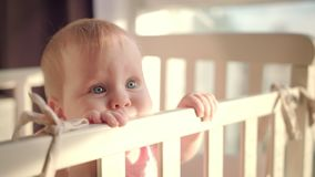 Bebé que se coloca en cama en casa Retrato del soporte del bebé en choza Ojos del bebé almacen de video