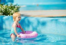 Bebé que se coloca en piscina con el anillo inflable Fotos de archivo libres de regalías